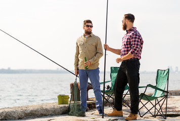 Tuinposter Ontspanning leisure and people concept - male friends with fishing rods and beer on pier at sea