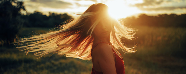 Young blond woman stands on meadow with loose hair lit by sun.