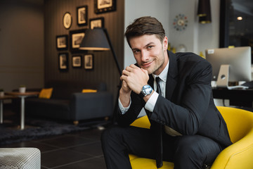 Portrait of beautiful young businessman wearing formal black suit sitting on armchair in hotel hall Fotobehang