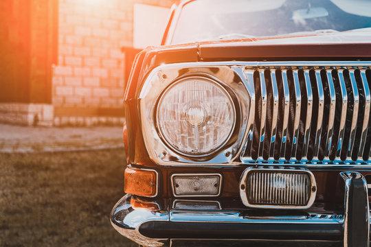 Close up of headlight of custom tuned classic retro lowrider car in sunlight