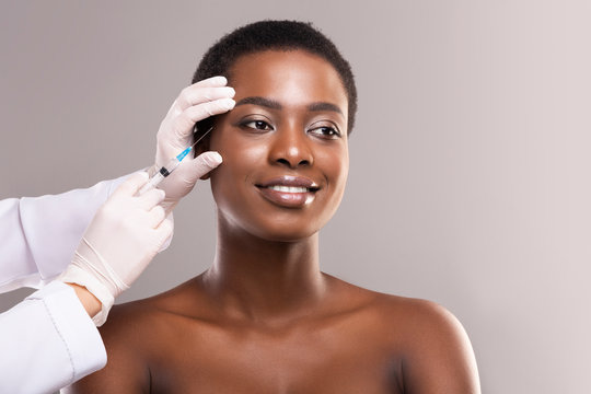 Young black woman getting beauty injection under skin