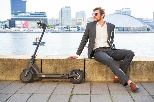 Young modern man using electric scooter on city street. Modern and ecological transportation concept.