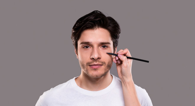 Surgeon drawing marks with pencil on male face