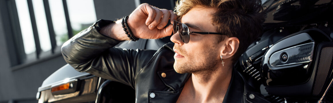 panoramic shot of young man sitting near motorcycle and holding sunglasses while looking away