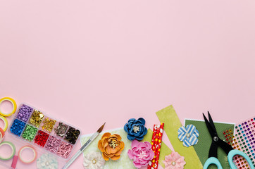Paper flowers, tools, paper and scrapbooking items on pink background. Scrapbooking, top view, empty space for text