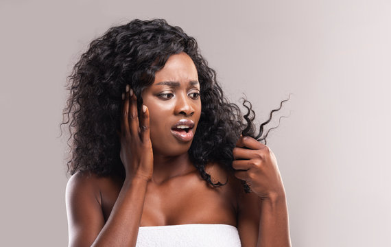Sad african woman looking at dry edges of damaged hair