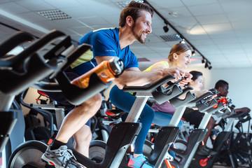 Europäischer Mann und Freunde auf dem Trainings Bike im Fitnessstudio