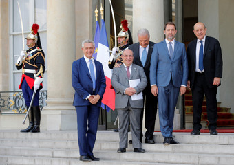 Filippo Grandi, Antonio Vitorino, Dimitris Avramopoulos, Christophe Castaner and Jean-Yves Le Drian pose for a photo as they arrive for a meeting with French President Emmanuel Macron at the Elysee Palace in Paris