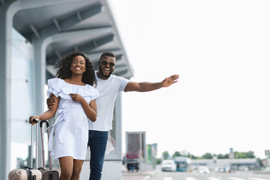 Young african couple standing near airport trying to stop car