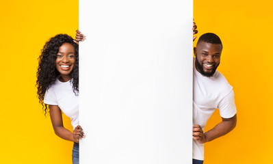 African couple posing with white empty board Fototapete