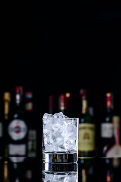 glass of roks with ice on the bar