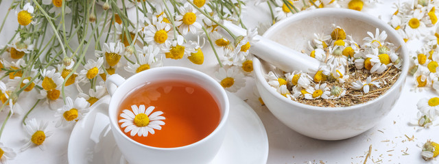 Photo sur Plexiglas The Rural still-life - cup of brewed chamomile tea on the background of a bouquet of daisies, closeup