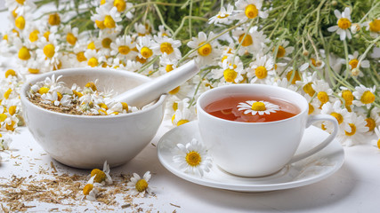 Rural still-life - cup of brewed chamomile tea on the background of a bouquet of daisies, closeup
