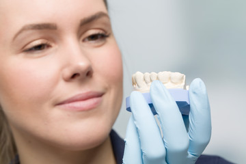 female dental technician cheks quality of an artificial dention