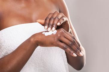 Fototapete - African girl applying body milk on her hand.