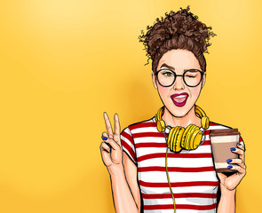 Winking woman in glasses with head phones makes peace gesture  Pop art girl holding coffee cup.