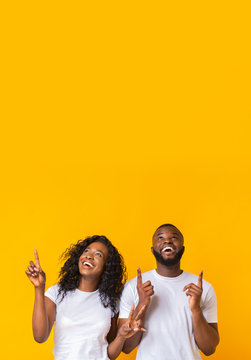 Happy african-american man and woman pointing fingers upwards