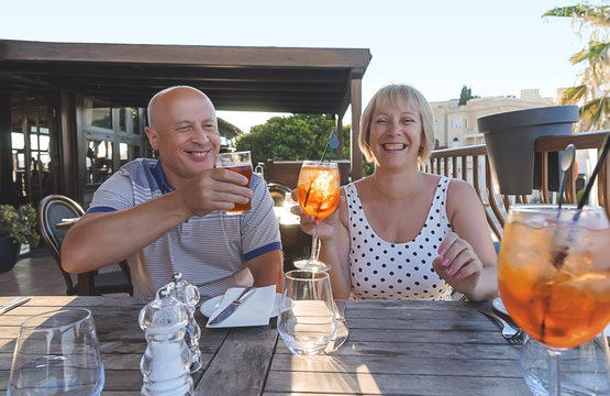 Middle-aged couple of baby boomers people smiling and enjoying with drinks in restaurant on sunny summer evening