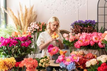 Obraz Beautiful blonde florist woman picks up flowers and creates wonderful bouquet - fototapety do salonu