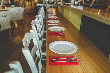 Close-up view of the row of the chairs and table with the white plates and the flatware on the red serviettes. Contemporary interior of the restaurant. Modern decoration in bright colors.