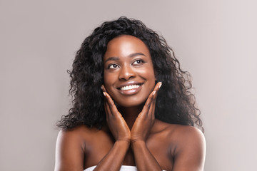 Fototapete - Young black woman applying moisturizer cream on her face