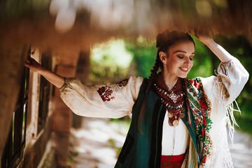 Beautiful girl in a traditional Ukrainian dress smiles Wall mural