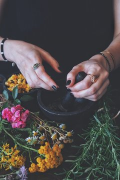 Female wiccan witch grinding summer herbs and flowers with pestle and mortar. Colorful fresh flowers and rosemary on a black table. A woman wearing vintage jewelry holding pestle in her hand. Vertical