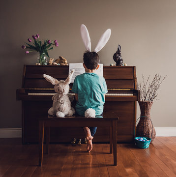 Boy wearing bunny ears playing piano with stuffed rabbit beside him.