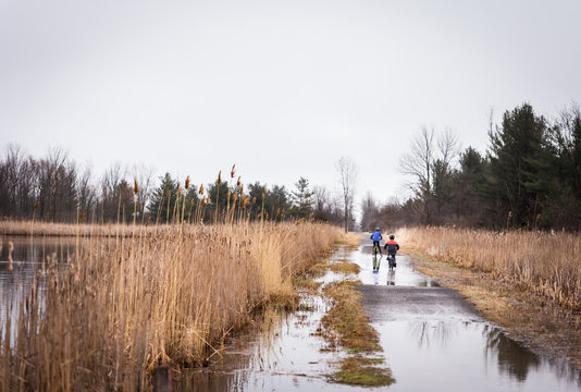 Two boys riding their bikes through a large puddle on a flooded trail.