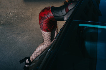 cropped view of sexy woman in red skirt standing near car