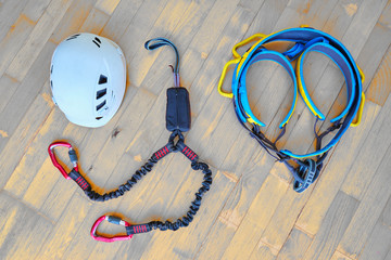 Via ferrata set: helmet, via ferrata lanyards and shock absorber, climbing harness. Top down photo of essential klettersteig gear laid out on wooden floor with a diagonal pattern.