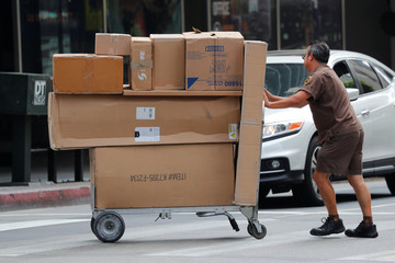 A UPS driver pushes a load of packages from his truck to a building in downtown Los Angeles