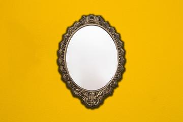 Vintage mirror on retro yellow wall background texture