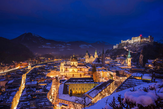 Elevated view of Salzburg city by night on a winter evening with the roofs covered with snow and the Hohensalzburg Castle