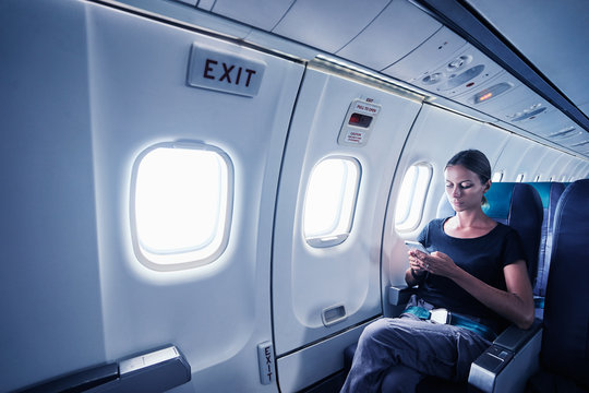 Travel and technology. Young woman in plane using smartphone while sitting in airplane seat.