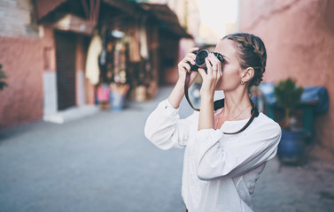 Tourism and technology. Happy young woman taking photo of  Marrakesh old town. Traveling by Morocco.