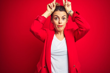 Young beautiful business woman standing over red isolated background doing funny gesture with finger over head as bull horns