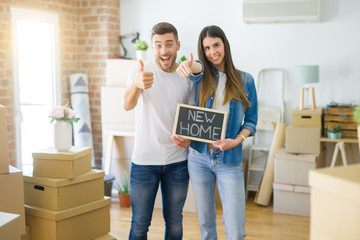 Young beautiful couple holding blackboard with new home text at new house happy with big smile doing ok sign, thumb up with fingers, excellent sign
