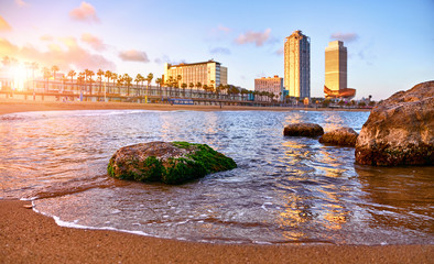 Barcelona, Spain. Panoramic view at Barceloneta beach from sea. View with stones. Sunset landscape with blue sky. Sandy coastline with palms and waves of surf. Popular touristic vacation destination. Fototapete