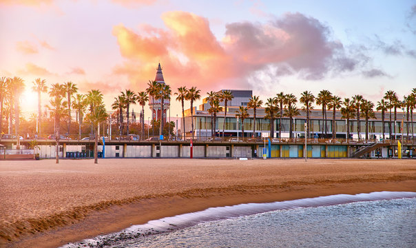 Barcelona, Spain. Panoramic view at Barceloneta beach from sea. View with stones. Sunset landscape with blue sky. Sandy coastline with palms and waves of surf. Popular touristic vacation destination.