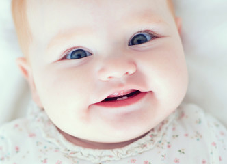 top view of infant baby girl, smilyng with her first two teeth