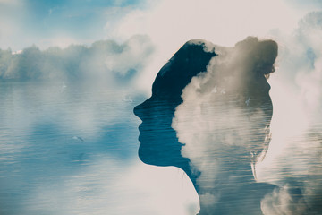 Silhouette of young woman head on background of clouds and birds