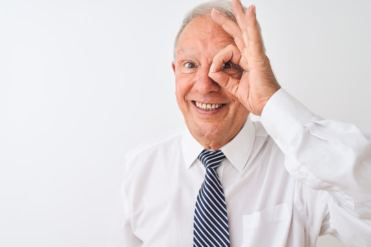 Senior grey-haired businessman wearing tie standing over isolated white background with happy face smiling doing ok sign with hand on eye looking through fingers