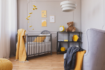 stylish grey and yellow baby bedroom with crib and industrial black metal shelf
