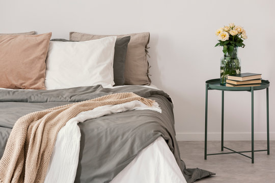 White roses in glass vase and books on stylish nightstand next to big bed with linen pillows and cozy blanket