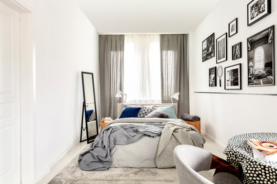 Small bedroom interior with king size, mirror, and black and white photos on the wall