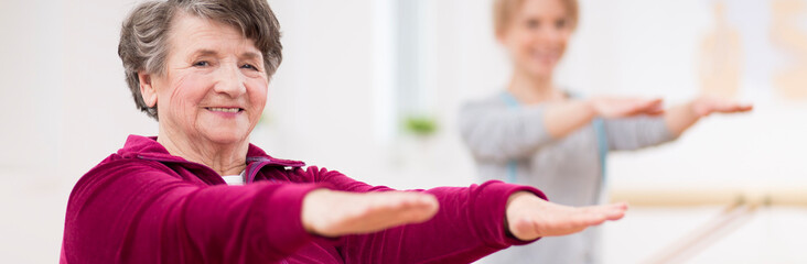 Panoramic view of senior grey woman exercising at hospital physiotherapy center