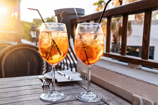 Two wine glass of cold cocktail Aperol spritz on background of restaurant. Traditional Italian Aperitif Cocktail concept