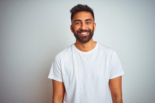 Young indian man wearing t-shirt standing over isolated white background with a happy and cool smile on face. Lucky person.