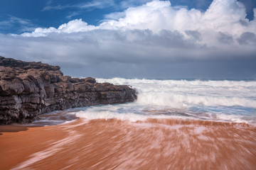 Wall Mural - waves crashing on sand and rock